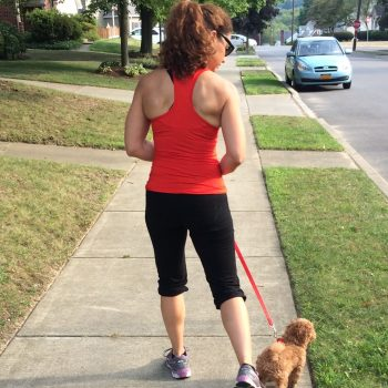Kristina Martemucci walking a toy Poodle down a sidewalk.
